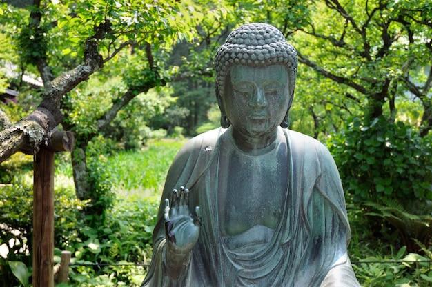 Statue de bouddha japonais dans l'environnement de jardin zen à kamakura, japon