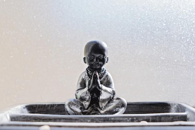 Statue de bouddha en position du lotus contre le verre