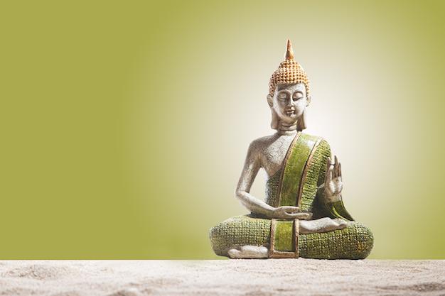 Statue de bouddha verte et dorée, sur le sable. méditation, spiritualité et concept zen.