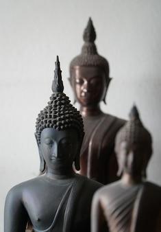Statue de bouddhas ancienne noir vintage au milieu d'une autre statue de bouddhas