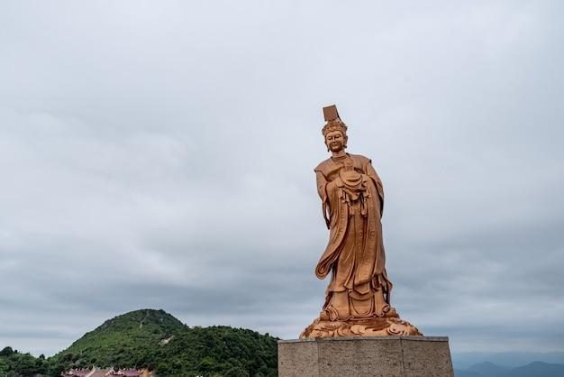 La statue en bronze de la déesse religieuse chinoise par temps nuageux