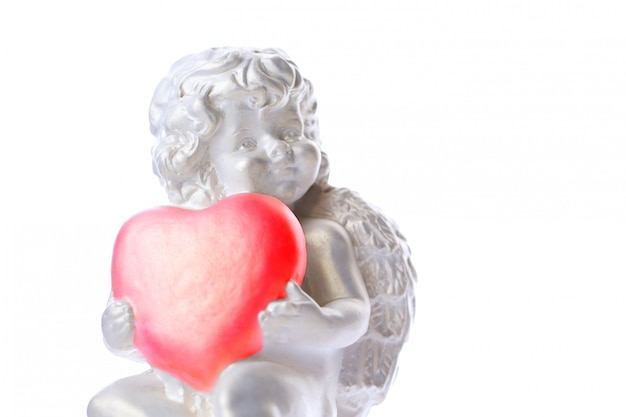 Statue de chérubin isolé sur une surface blanche, ange détient le coeur, amour