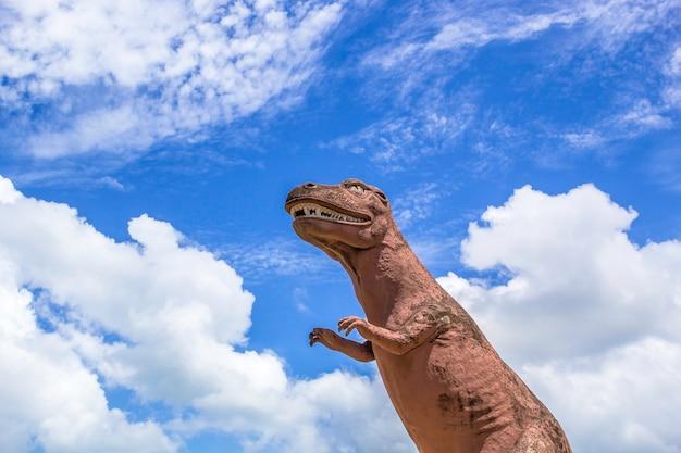 Statue de dinosaure avec un ciel bleu