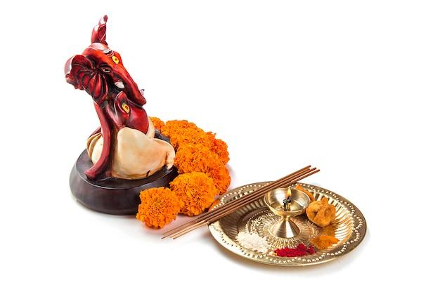 Statue du dieu hindou ganesha avec arrangement de culte sur une surface blanche.