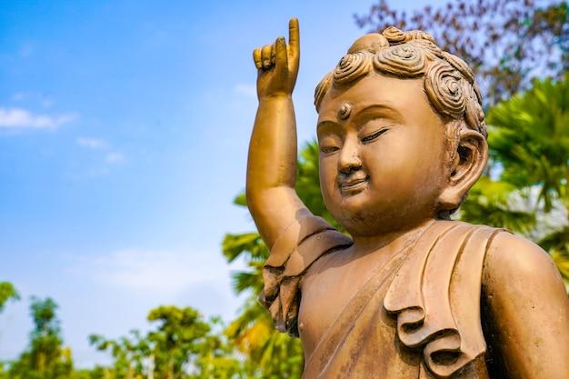 La statue du petit bouddha en bronze et cuivre pointe le doigt vers le ciel.