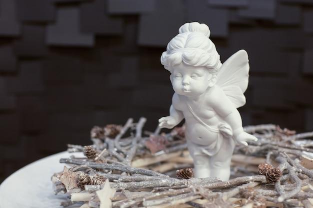 Statue d'une fille ange avec des ailes et une couronne de brindilles sur fond sombre pour noël