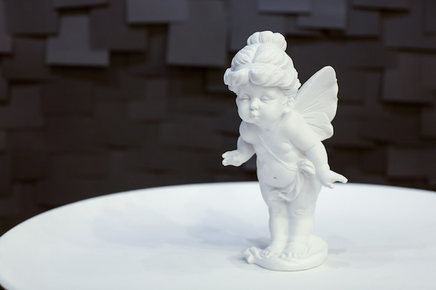 Statue d'une fille ange avec des ailes sur une plaque blanche sur fond sombre