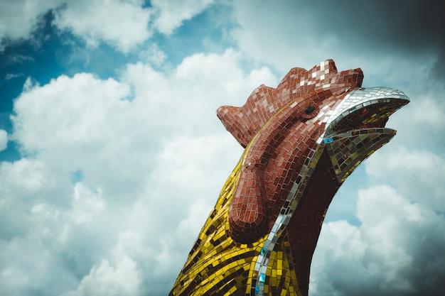 Statue de grosse tête de poulet sur fond de ciel bleu