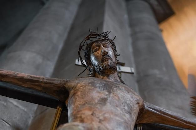 Une statue de jésus accrochée à une croix dans une église