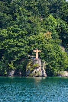 Statue de jésus christ sur le lac de lucerne en suisse. la statue a été réalisée par josef vetter.