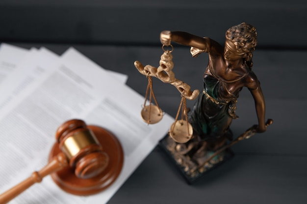 Statue de la justice et marteau sur fond gris