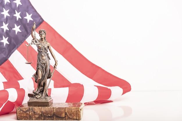 La statue de la justice themis ou iustitia la déesse de la justice aux yeux bandés contre un drapeau de l'un...