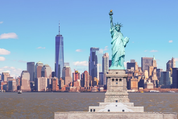 La statue de la liberté avec le one world trade building center sur la rivière hudson et l'arrière-plan du paysage urbain de new york, monuments de lower manhattan new york city.