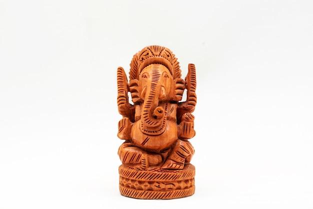 Statue miniature en bois du dieu hindou ganesha sur une surface blanche