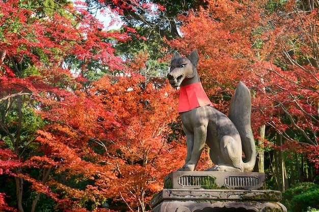 Statue de renard et feuilles d'automne au sanctuaire fushimi inari.