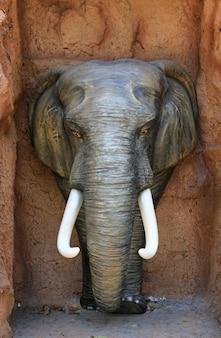 La statue de la tête d'éléphant sur fond de pierre.