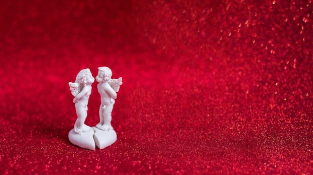 Statuette de deux anges qui s'embrassent sur fond rouge avec bokeh, saint valentin et amour