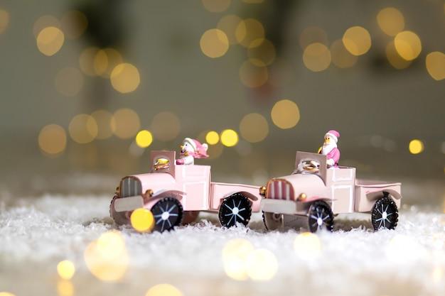La statuette du père noël monte sur une voiture miniature avec une remorque pour cadeaux
