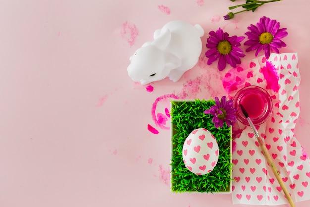 Statuette de lapin près de l'oeuf et des fleurs