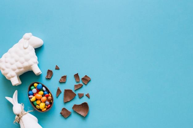 Statuettes de moutons et de lapin près d'oeufs en chocolat