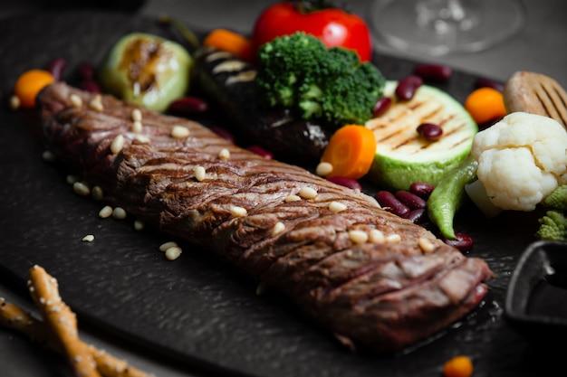 Steak d'agneau aux légumes grillés et grillés sur une planche en pierre noire