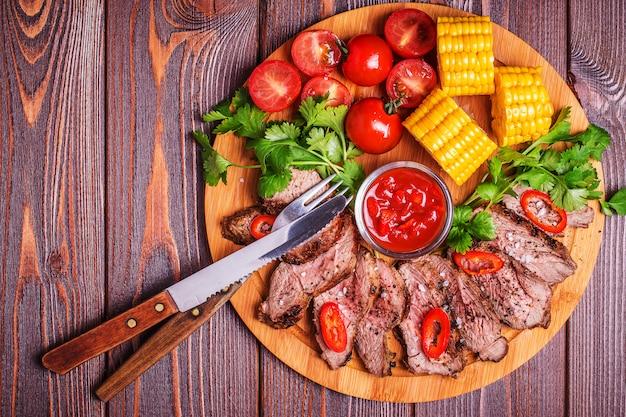 Steak d'agneau bbq avec légumes et herbes sur bois foncé.