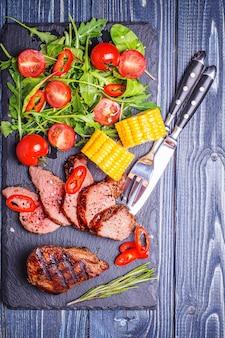 Steak d'agneau bbq avec salade de légumes et maïs sur bois foncé.