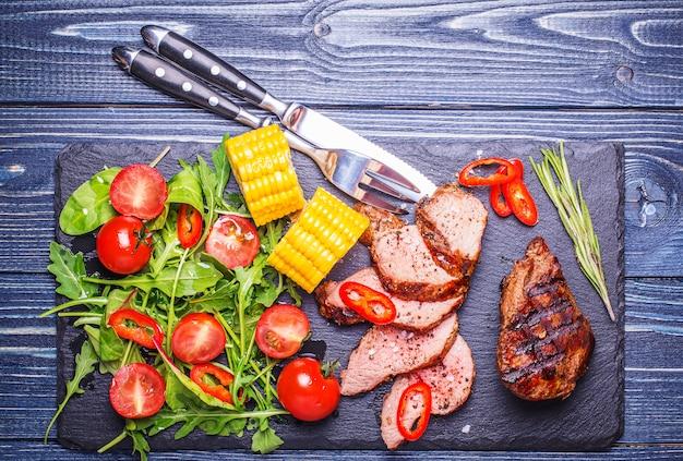 Steak d'agneau bbq avec salade de légumes et maïs sur fond de bois foncé.