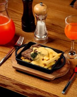 Steak d'agneau avec frites et fromage fondu