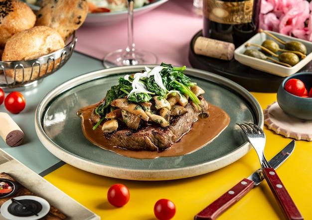 Steak d'agneau garni de champignons sautés et d'épinards