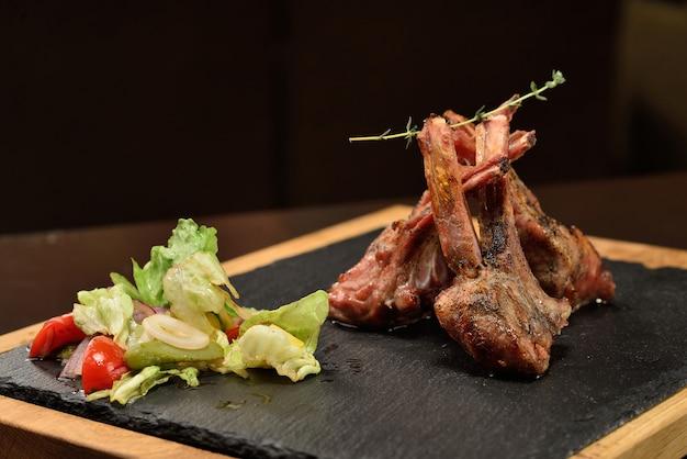 Steak d'agneau avec salade sur fond sombre