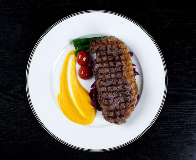 Steak bien cuit avec tomates cerises et asperges