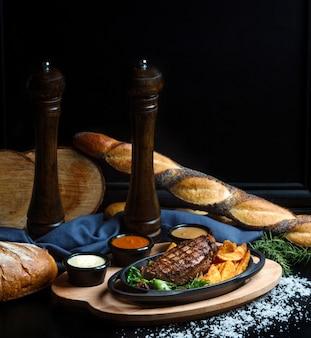 Steak bien fait avec des pommes de terre frites et des sauces faites maison