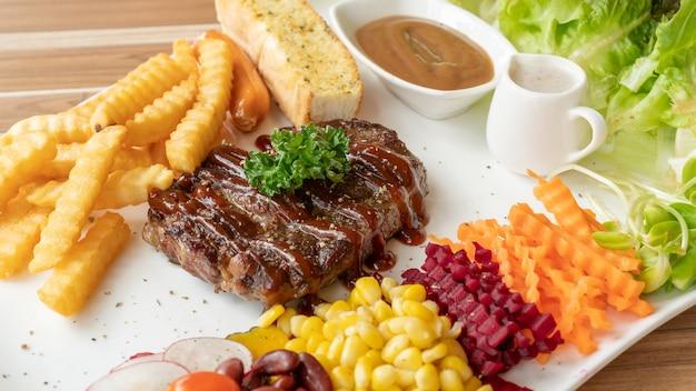 Steak de bifteck, frites et légumes sur une assiette blanche.