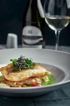 Steak blanc de poisson grillé sur un oreiller de légumes et sauce jaune, avec tomates et herbes fraîches. poisson sur une plaque blanche avec du vin blanc sur dark
