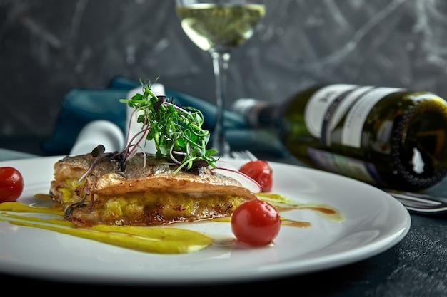 Steak blanc de poisson grillé sur oreiller de légumes et sauce jaune, avec tomates et herbes fraîches.