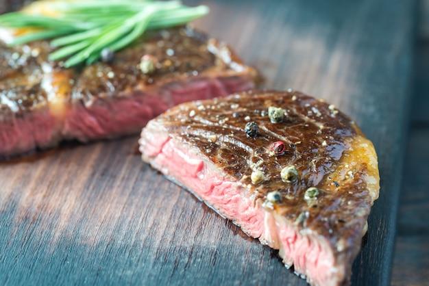 Steak de boeuf au romarin frais sur la planche de bois