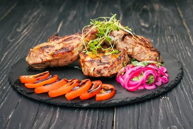 Un steak de boeuf aux épices et légumes, sur une table en bois