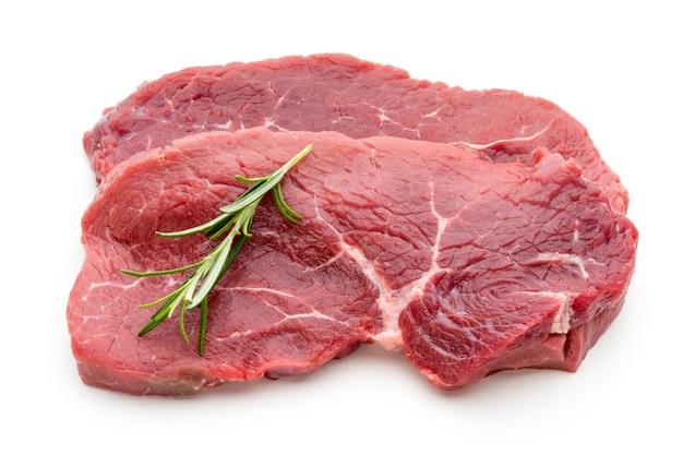 Steak de boeuf bio cru frais isolé sur une surface blanche.