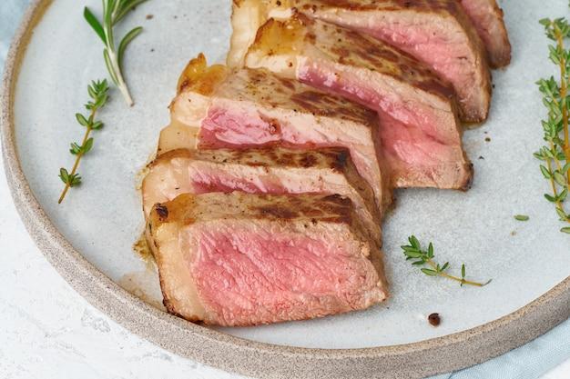 Steak de boeuf cétogène régime cétogène, contre-filet sur plaque grise sur blanc.