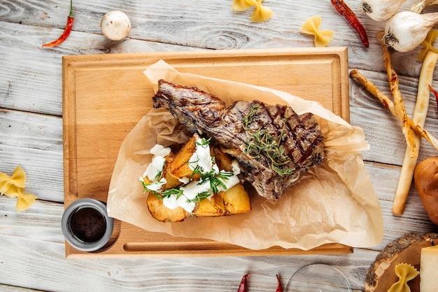 Steak de boeuf cowboy avec pommes de terre au four et crème sure