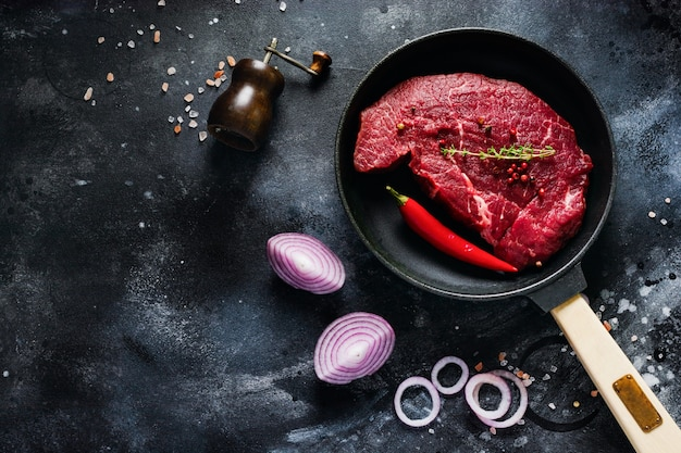 Steak de boeuf cru aux épices, oignons et piment dans une poêle à frire en fonte pour faire frire sur fond d'ardoise foncée ou de béton. vue de dessus.