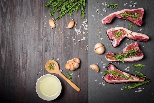 Steak de boeuf cru frais et ingrédients sur planche de pierre noire sur table en bois noir