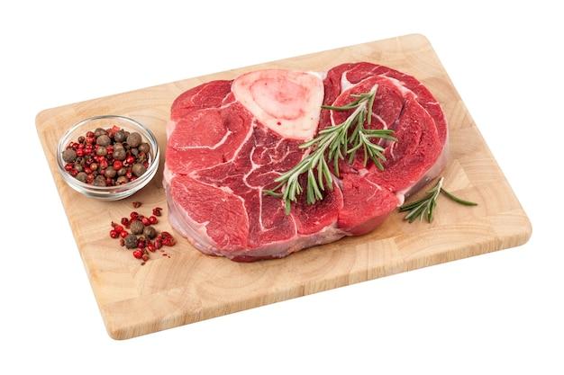 Steak de boeuf cru frais avec os sur planche à découper sur fond blanc