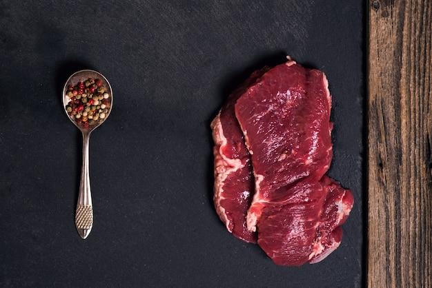 Un steak de boeuf cru en marbre sur fond noir