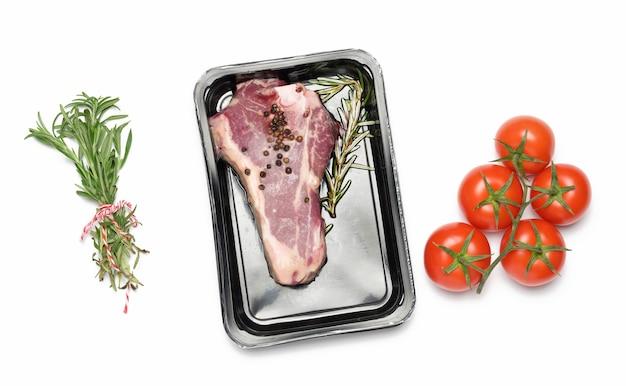 Le steak de boeuf cru de new york est emballé dans un récipient en plastique et scellé sous vide