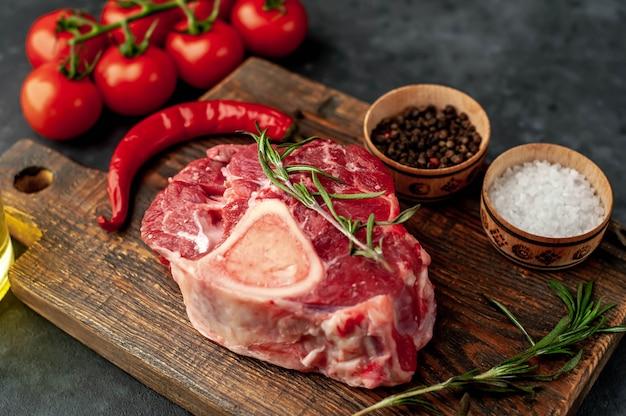 Steak de boeuf cru avec os et épices sur fond de pierre