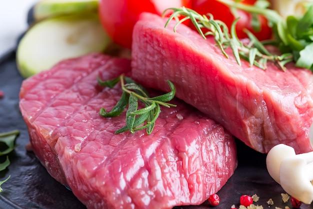 Steak de bœuf cru sur l'os avec des légumes frais dans un grill