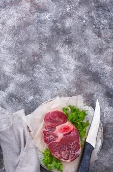 Steak de boeuf cru ossobuco sur planche à découper