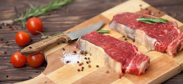 Steak de bœuf cru ribeye cuisson avec des ingrédients. vue de dessus avec espace copie